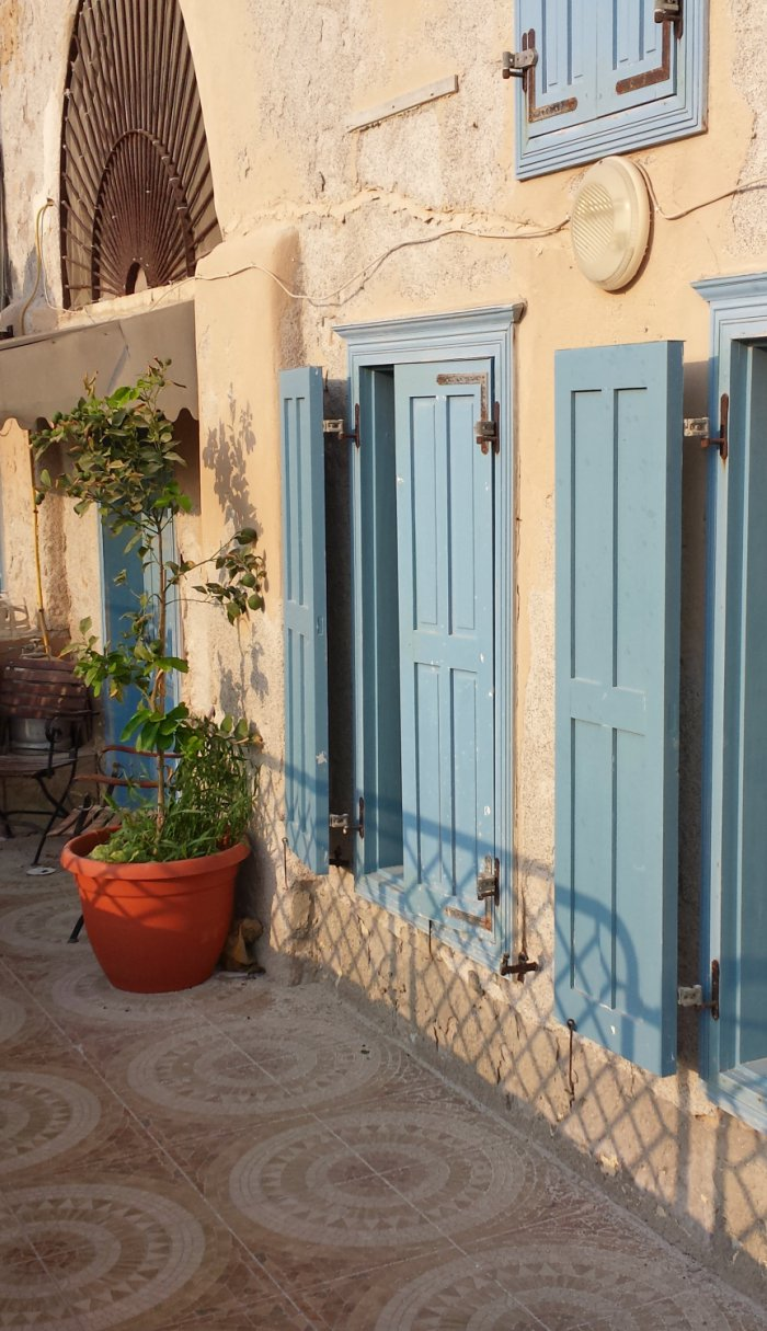 Rustic style home with a taste of Provence with pale blue wooden window shutters and plant round the door