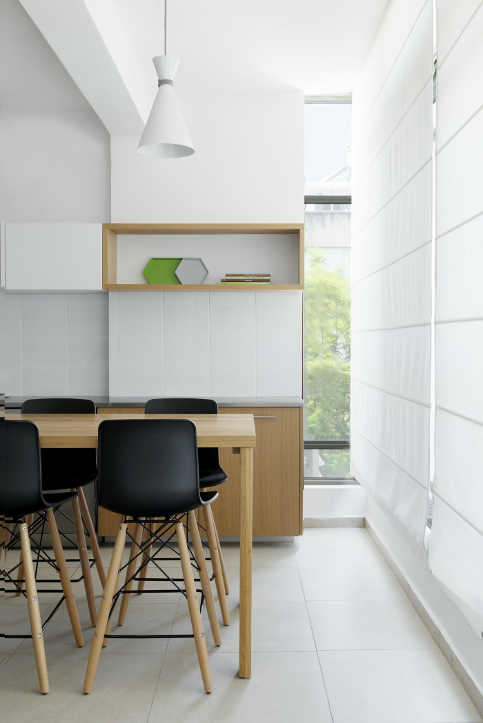 Scandi style minimalist kitchen diner in white, oak and black designed by architect Itai Palti